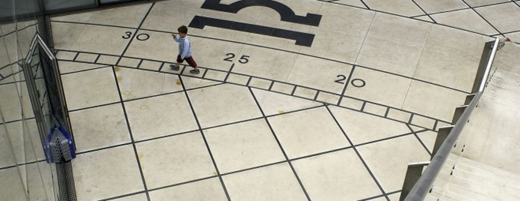 Begehbarer Sektor mit Treppe rechts, Tierkreiszeichen Waage und einem Knaben zum Größenvergleich. https://parisladefense.com/en/discover/artwork/la-carte-du-ciel